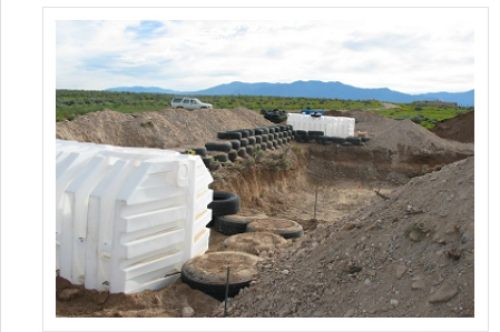 Early stage of earthship construction.  Notice the dirt and tire walls and the cisterns.
